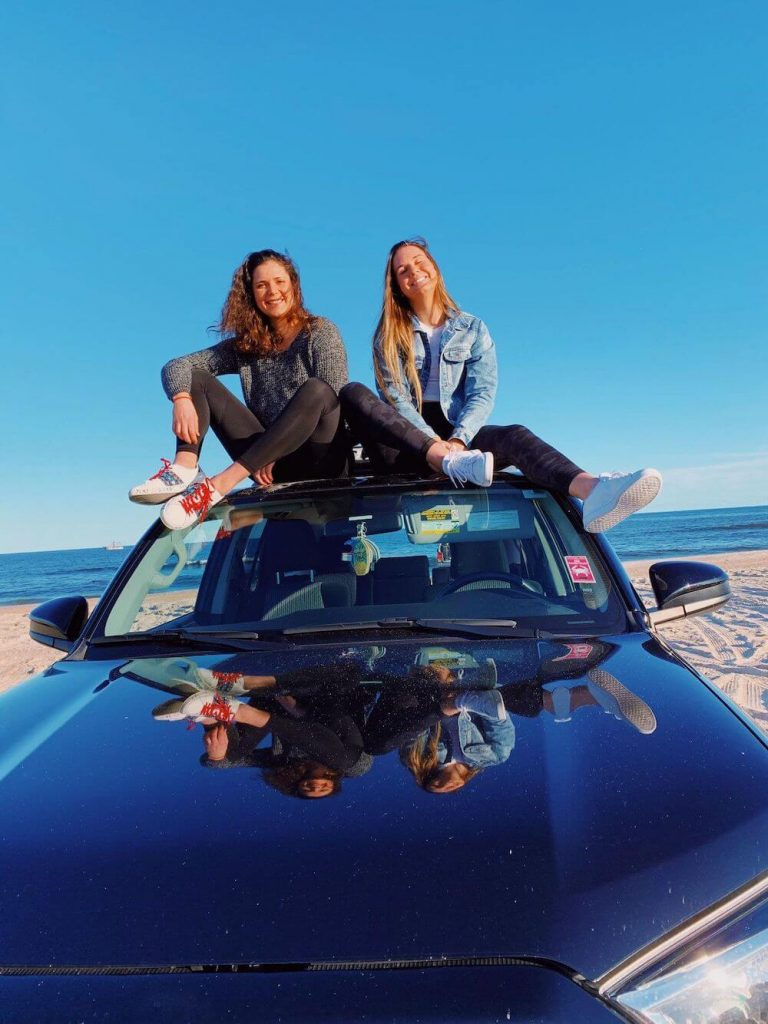 two girls smiling sitting on the roof of a car at the beach