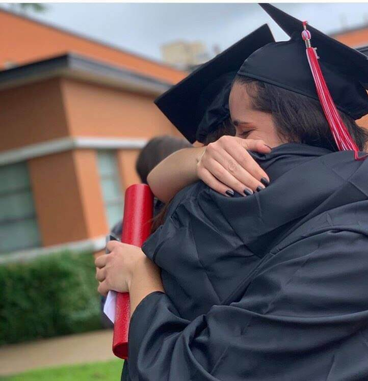 two girls hugging after graduation